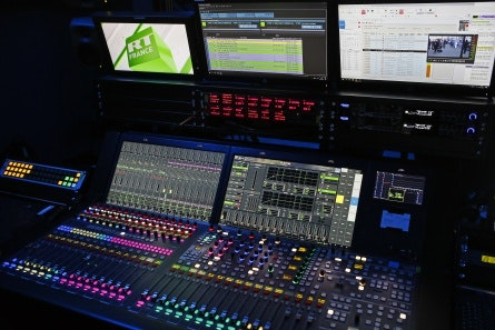 Knobs, buttons, and monitors in a dark room