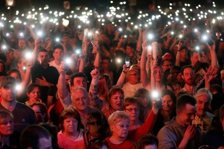 People holding cell phones up like candles in a crowd