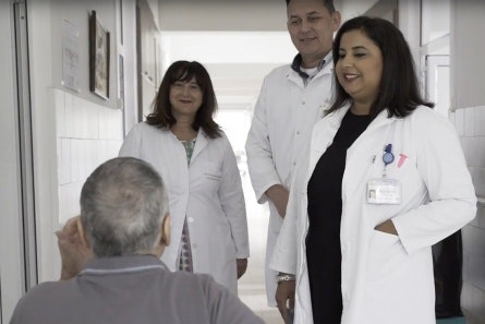 Doctors speaking with a patient in a hospital hallway