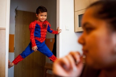 A boy in a costume climbs a door jamb