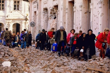 A line of Croatians walk through rubble