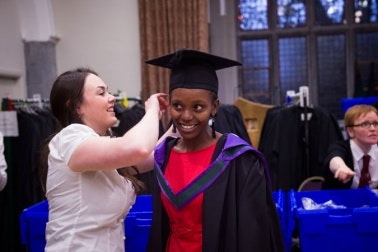A woman helping another woman with a graduate robe