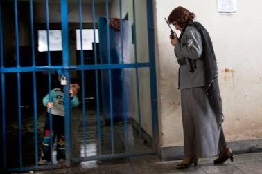 Boy behind bars with woman guard