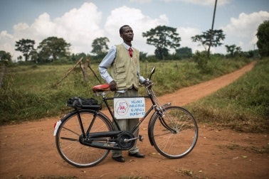 A man standing next to bicycle