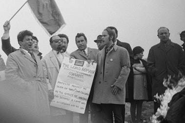 A group celebrating and holding a flag.