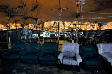 Armchair and antennas on a rooftop, with cityscape in the background
