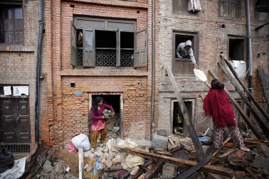 Women retrieve belongings from rubble