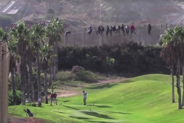 Migrants on a fence above a golf course