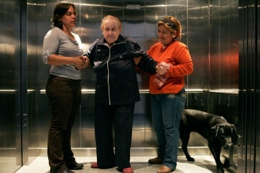 A doctor and a relative help a patient off an elevator