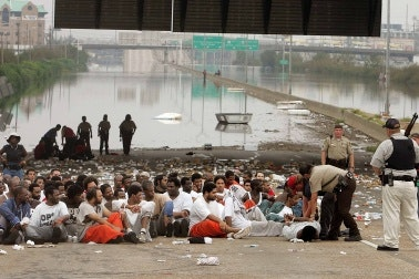 Inmates sitting on a flooded highway