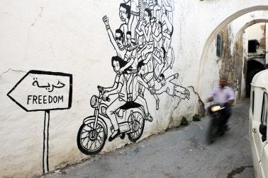 Man on a motorbike rides past wall art of a motorbike.