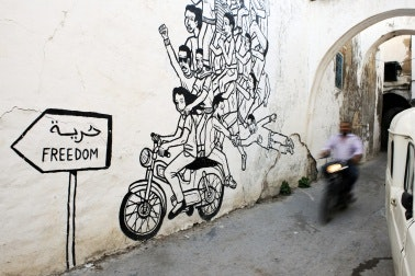 Man on a motorbike rides past wall art of a motorbike.