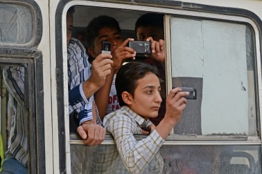 Young people film out of a bus window