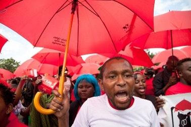 Demonstrators holding red umbrellas