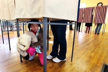 A girl crouching under a voting booth