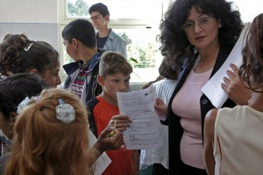 Teacher handing out forms to students