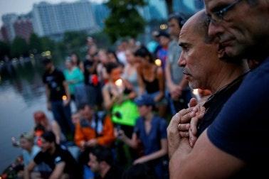Two men embrace at a vigil