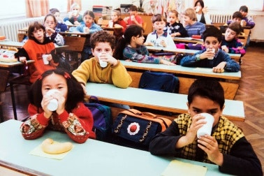 Children at school desks drinking milk