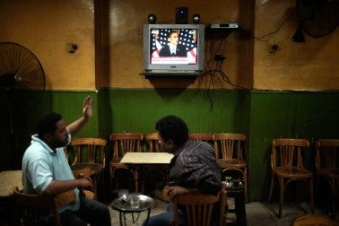 People in a cafe watch President Obama on a TV