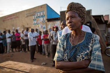 A woman standing in a line at sunset