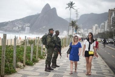 People walking passed armed soldiers