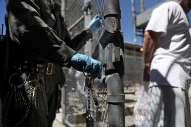 An officer unlocking a fence in the recreation area of a prison