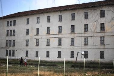 Two people walk near a prison building