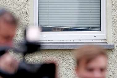 A boy peaks out of a window at a person holding a video camera