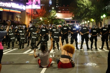 Two people sit in front of a row of police officers