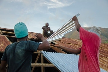 Three men repairing a roof