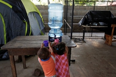 Two children with cups at a water jug