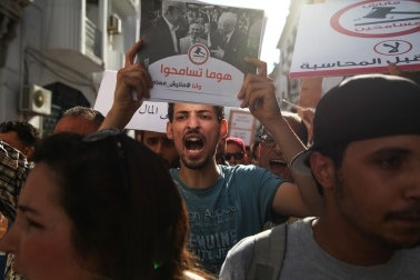 A man shouting and holding a sign in a crowd