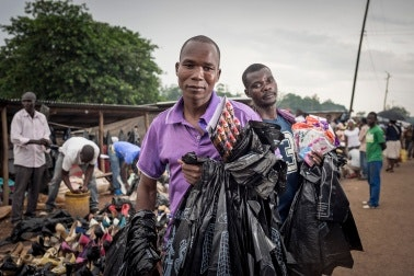 Men in a market holding plastic bags