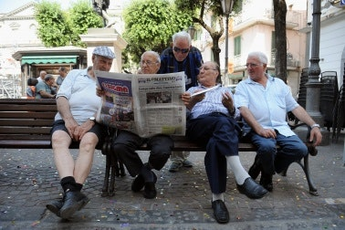 Men sitting on a park bench holding a newspaper