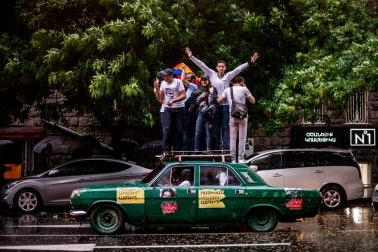 A group of people standing on top of a green car