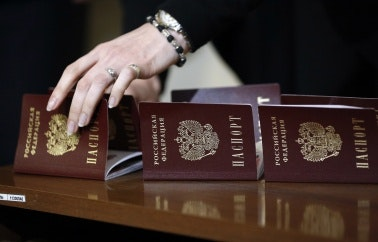 A woman's hand reaching toward a passport