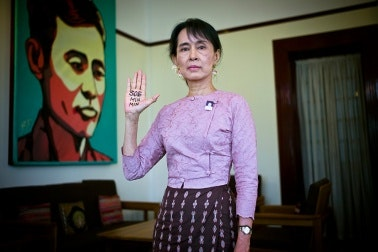 Aung San Suu Kyi raising hand with writing on it.