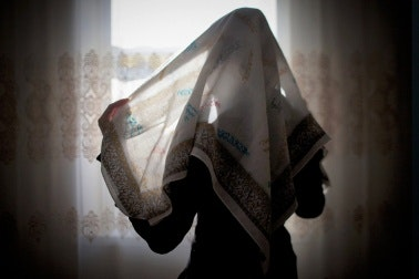 A young woman with her face covered