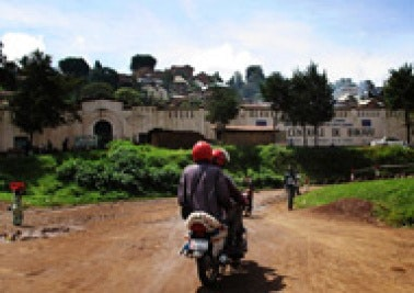 Two men on a motorcycle in front of Bukavu Central Prison