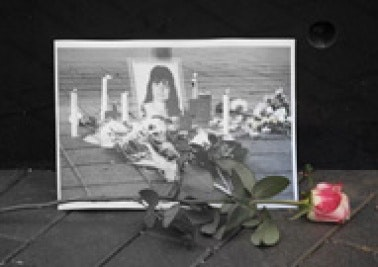 Vigil; rose in front of a photograph of a woman's picture surrounded by candles