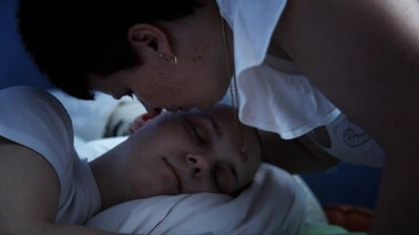 Woman kissing son who is lying down