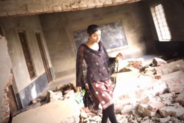 A young woman in a damaged classroom