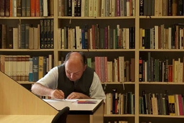 A man writing at a desk