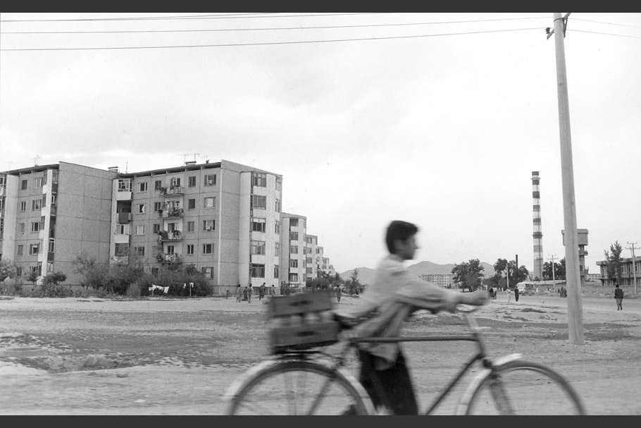 A bicyclist in front of a building.