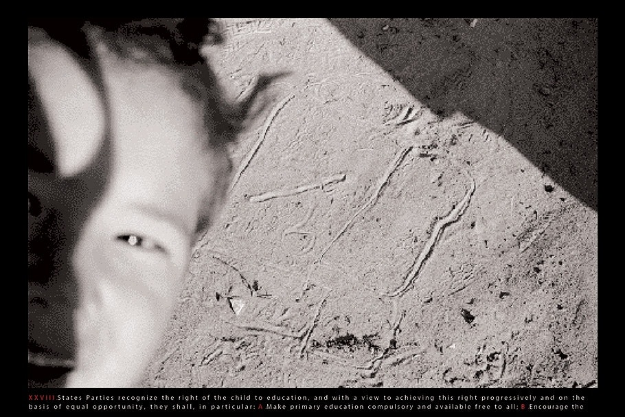 Close up of a boy's face against a textured wall.
