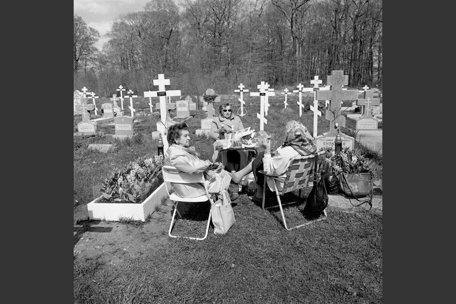 Three women sitting in lawn chairs in a cemetery.