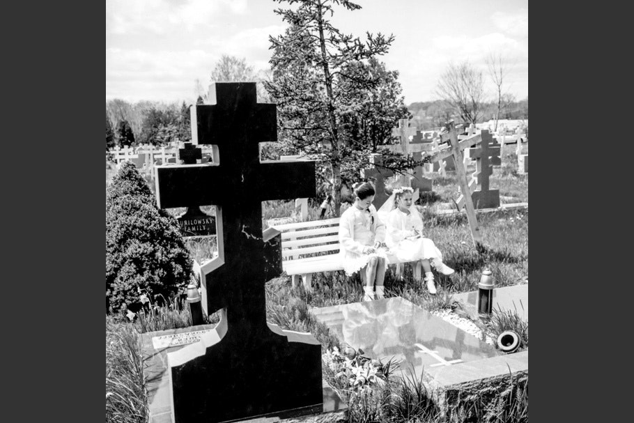 Two girls on a bench in a cemetery.