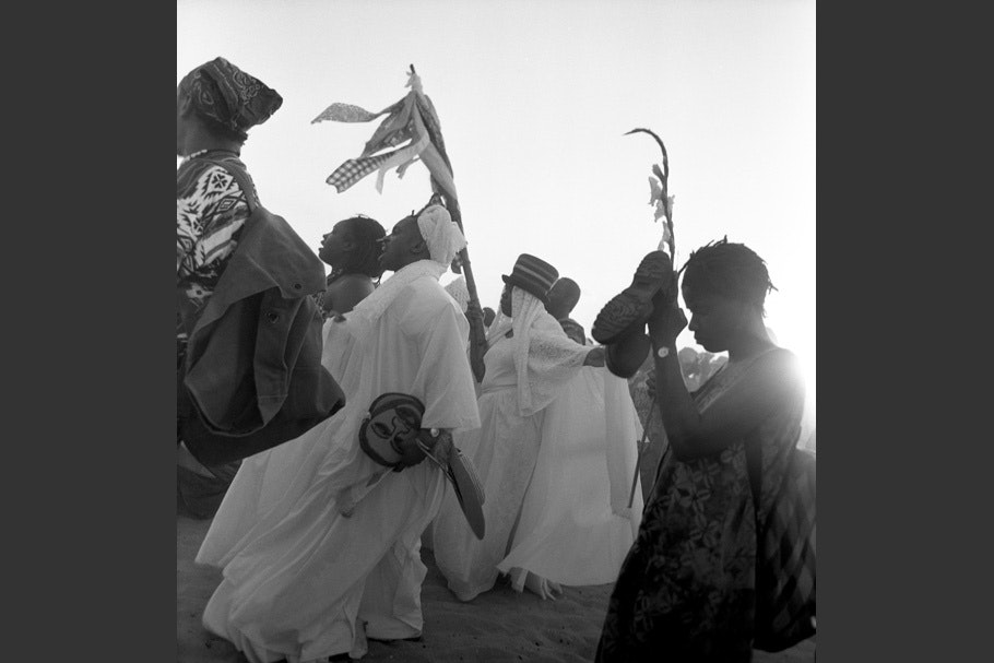 People in ceremonial clothing on a beach.