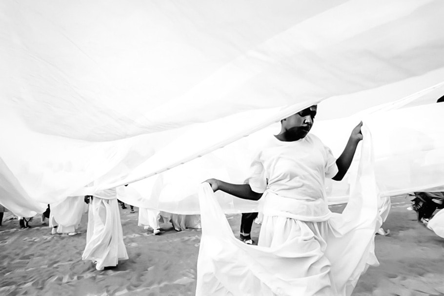 People walking under white fabric on a beach.