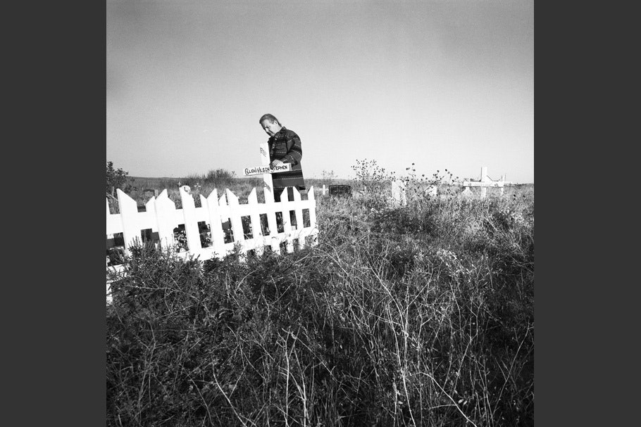 A man stands at a fenced grave.